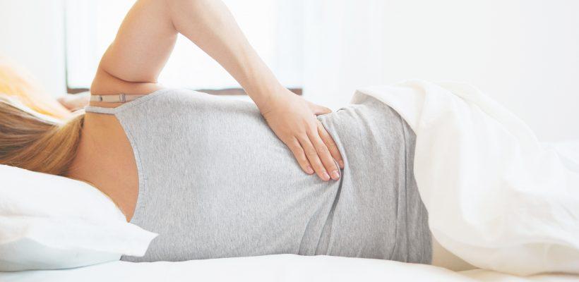 Donna distesa a letto con dolore alla schiena